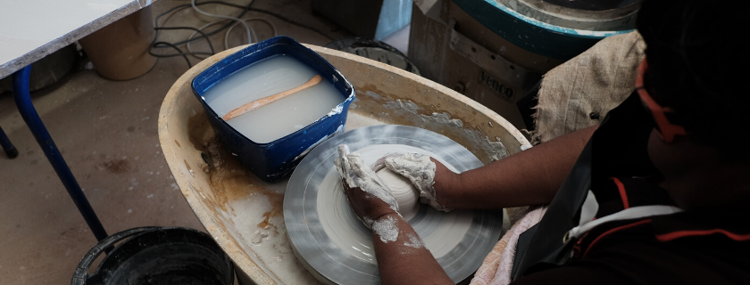 Veronica Coulthard working with clay on the pottery wheel at Ngapala Arts, Copley SA.