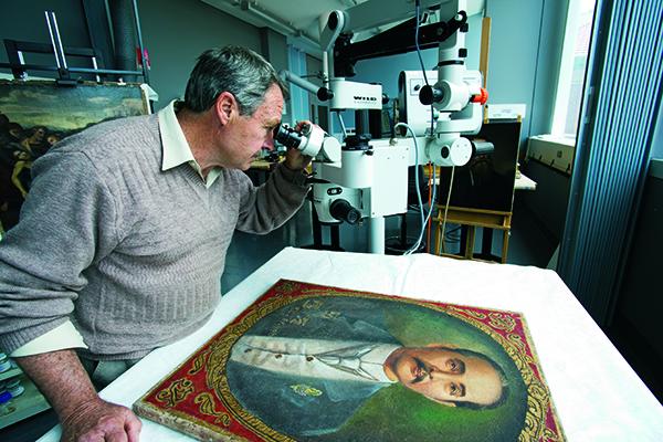 Photo: Chris Payne examining artwork
