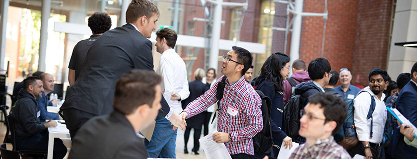 student shaking hands with recruiter